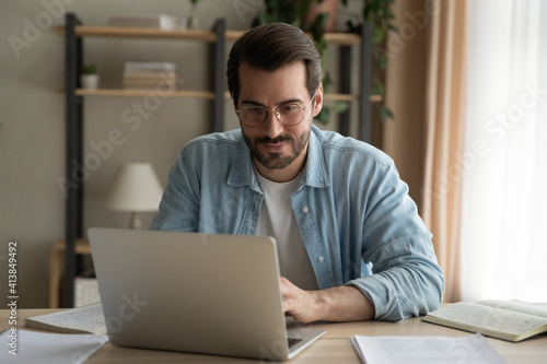 Fototapeta Attentive millennial male manager employee busy at telework at quarantine time study documents in corporate network from home pc. Concentrated young man specialist doing remote computer work on laptop obraz