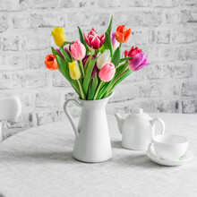 Bouquet Of Colorful Tulips, Ceramic White Teapot And Teacup On The Table In The Bright Kitchen. Cozy Home Concept