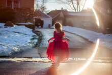 A Graceful Little Girl Holds Up Her Long Dress And Walks On Street