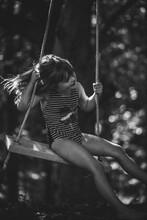 5 Year Old Girl Swinging On Tree Swing In Sunlight