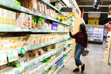 Woman Reading Label Products From Supermarket Dairy Shelf Area