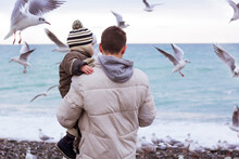 Father Holding His Son And Feeding Seagulls At The Beach. Family Time On The Seaside. Man With Boy Feeds Birds