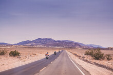 Three Motorbikes Ride On A Straight Road In Death Valley National Park
