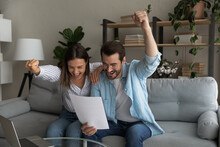 Excited Married Couple Hug On Couch Yell Yes Read Paper Letter About Getting Tax Refund Money Grant For Family Business. Amazed Young Spouses Overjoyed By Perfect Conditions Of Loan Mortgage Agreement