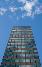 Tall Office Building Stands Alone Under A Sunny Blue Sky