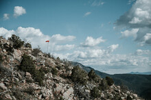 Mountain Top With Orange Windsock Blowing In The Wind And Blue Sky