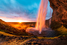 Seljalandsfoss Waterfall With A Great Sunset On Popular Tourist Destination, Where Tourists Can Walk Behind The Falling Waters, Part Of The Golden Circle
