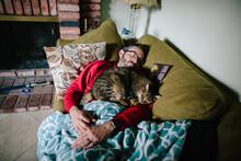 Man Asleep On A Couch With A Brown Tabby Cat Asleep On Him
