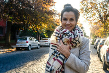 Portrait Of Smiling Young Woman With Scarf Standing On The Street