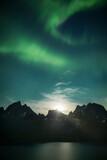 Aurora Boralis dancing in night sky above mountain peaks and lake, Greenland