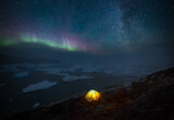 Tent overlooking icefjord and icebergs under starry night sky and aurora borealis