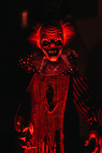 Closeup View Of A Scary Clown Mannequin Placed In The Dark Room With Red Lights On A Halloween Night