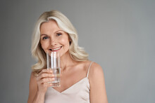 Smiling Healthy Thirsty Fit Mid Aged 50s Woman Holding Glass Drinking Water. Happy Mature Lady Hydrating Body With Clean Filtered Fresh Mineral Water For Skin Care, Beauty, Diet Nutrition Hydration.