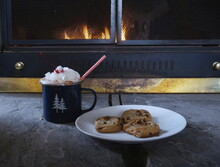 Hot Chocloate In Blue Tin Cup With Cookies In Front Of Fireplace