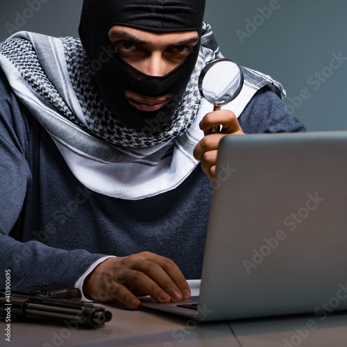 Fototapeta Hacker wearing balaclava mask hacking computer obraz
