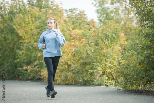 Obraz Young blond sporty female in activewear jogging down road in park among trees - fototapety do salonu