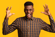 Portrait Of Young Angry Black Man Shouting With Rage Over Yellow Background