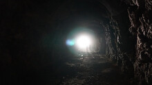 Light At The End Of A Long Cave And Children. The Sunlight Is Bright In The Eyes While In A Long, Dark Tunnel. Children Go To The Exit, Touching The Stone Walls. Rock Of An Artificial Mine.