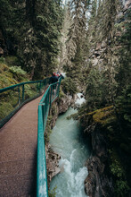 People Walking On Metal Catwalk Alongside The Flowing Water In Canyon.