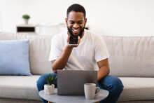 Black Man Using Voice Assistant Holding Cellphone Near Mouth Indoors