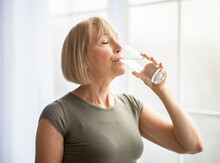 Fit Senior Woman Drinking Clear Water During Her Workout Break At Home. Healthy Lifestyle And Wellness Concept