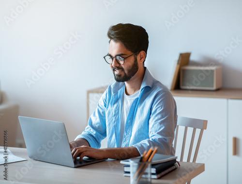 Photo Millennial arab freelancer man working online on laptop at home office
