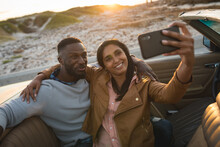Diverse Couple Sitting In A Convertible Car And Taking A Selfie