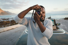 African American Man Standing By Convertible Car And Taking Photos With Camera