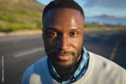 Portrait of african american man standing by the road looking at camera and smiling