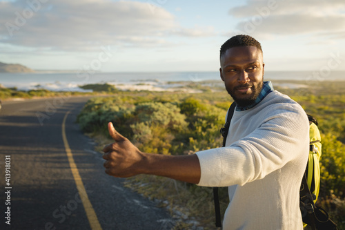 African american man standing by the road and hitchhiking