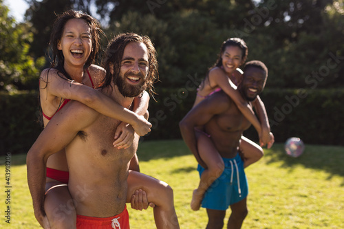 Diverse group of friends having fun and carrying on back at a pool party