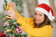 Pretty Woman Smiling Near Christmas Tree