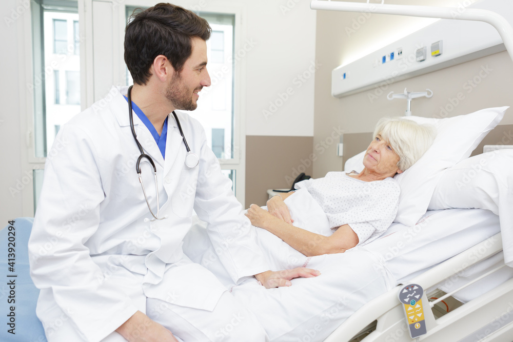 Fototapeta male doctor checking senior woman at home