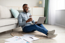 African Man Using Laptop Sitting On Floor Working At Home
