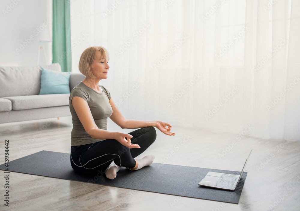 Fototapeta Peaceful senior woman meditating with closed eyes in front of laptop computer at home, copy space