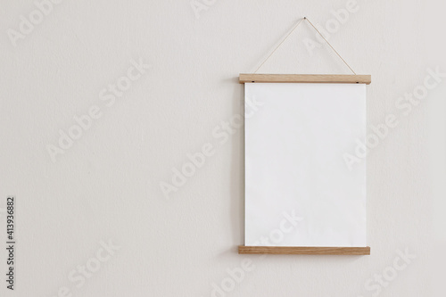 Fototapeta Blank wooden picture frame hanging on beige wall