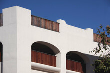 View Of A Corner Of A Downtown Public Parking Structure In Spanish Mission Revival Style With Blue Sky Above In Southern California