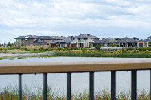 View Of A Row Of Modern Suburban Houses By A Lake Over The Fence Of A Viewing Platform. Concept Of Real Estate Development, The Housing Market, Australian Homes, And Natural Environment In New Suburb.