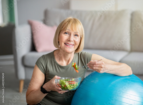 Obraz Exercise and healthy diet concept. Senior woman with fitball eating fresh vegetable salad at home - fototapety do salonu