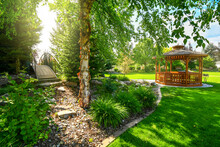 A Nicely Landscaped Garden And Back Yard With A Round Wooden Cedar Gazebo And A Bridge Over More Landscaping Areas.