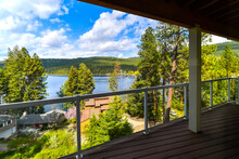 View Of Liberty Lake And The Mountains From An Upscale Home's Covered Deck In Neighborhood Of Homes In Liberty Lake, Washington, USA
