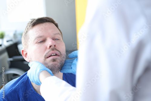 Fototapeta Doctor examines patient's thyroid gland in medical office obraz