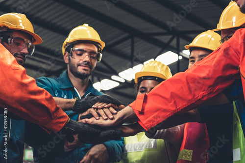 Skillful worker stand together showing teamwork in the factory . Industrial people and manufacturing labor concept .