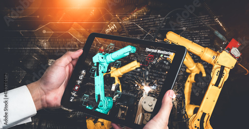 Obraz Engineer controls robotic arms by augmented reality industry technology application software. Smart robot machine in future factory working in concept of Industry 4.0 or 4th industrial revolution. - fototapety do salonu