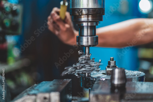 Fototapeta Professional machinist hand working with milling machine in metalworking factory, lathe metalworking industry concept obraz