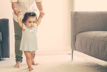 Focused Baby Girl In Pale Blue Dress Holding Moms Hands And Trying To Walk At Home. Full Length. Parenthood And Childhood Concept