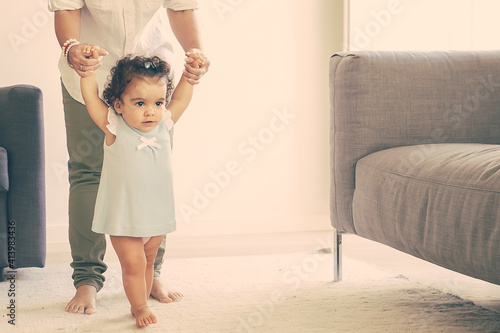 Obraz Focused baby girl in pale blue dress holding moms hands and trying to walk at home. Full length. Parenthood and childhood concept - fototapety do salonu