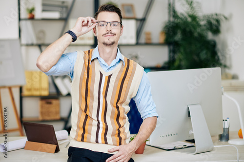 Portrait of smiling handsome young entrepreneur putting on glasses and looking a Fototapeta