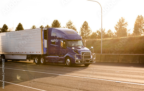 Canvas Print Dark blue big rig semi truck with grille guard transporting refrigerated semi tr