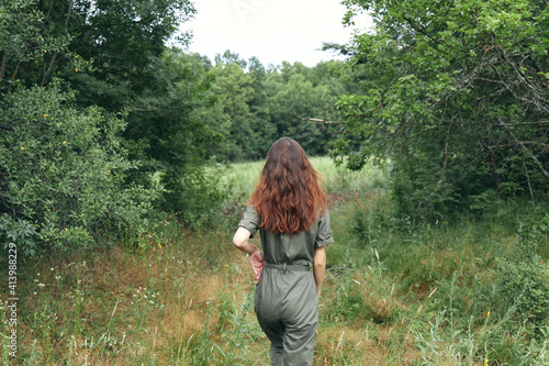 Fototapeta brunette woman in overalls on the meadow back view obraz